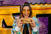 Happy beautiful young woman, smiling widely, holds tasty burger in two hands. Dressed in bright jacket and cap, in sunglasses. Outdoors, near the wall with graffiti.